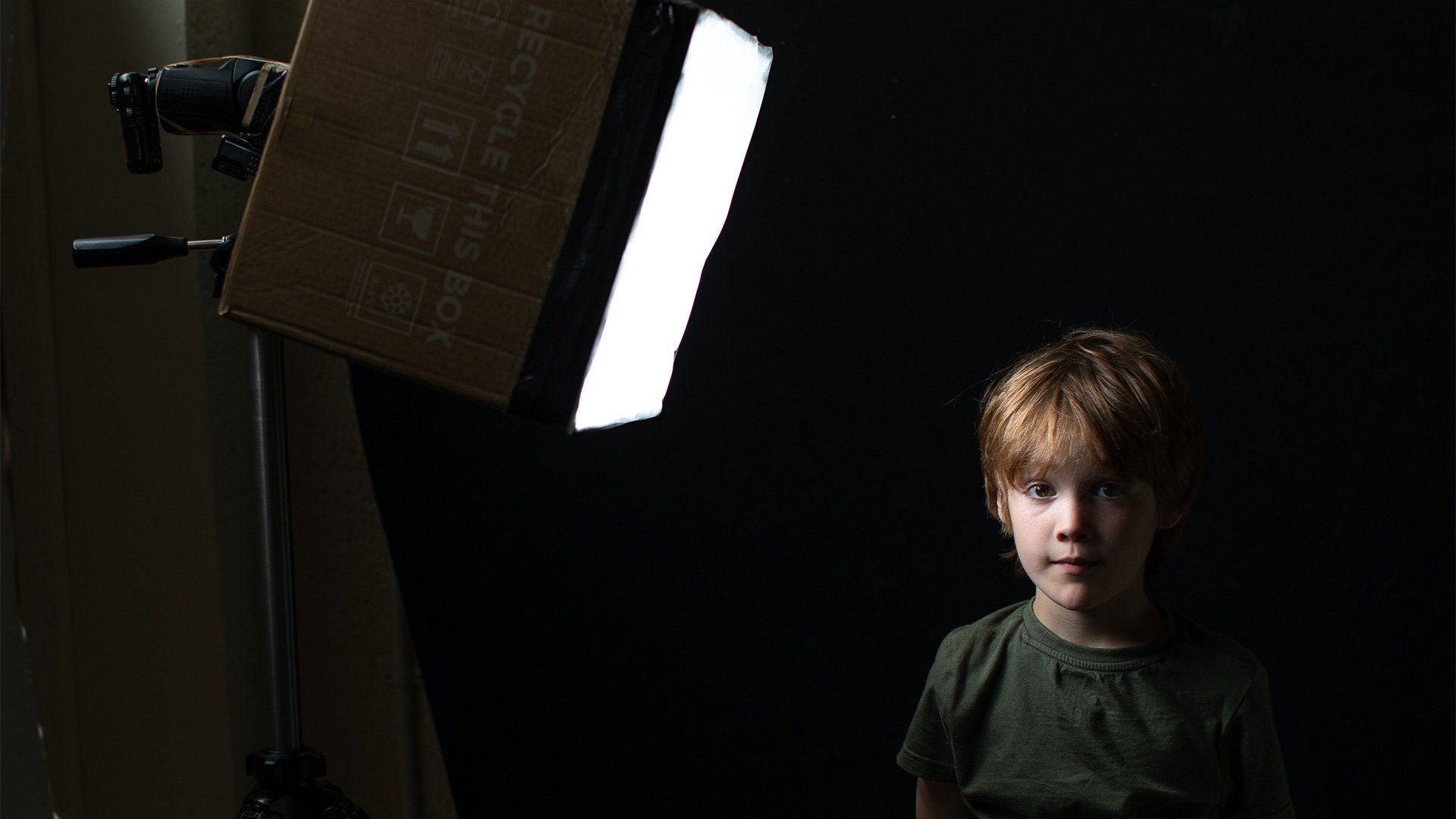 A young boy is lit from one side by a homemade softbox on a stand.